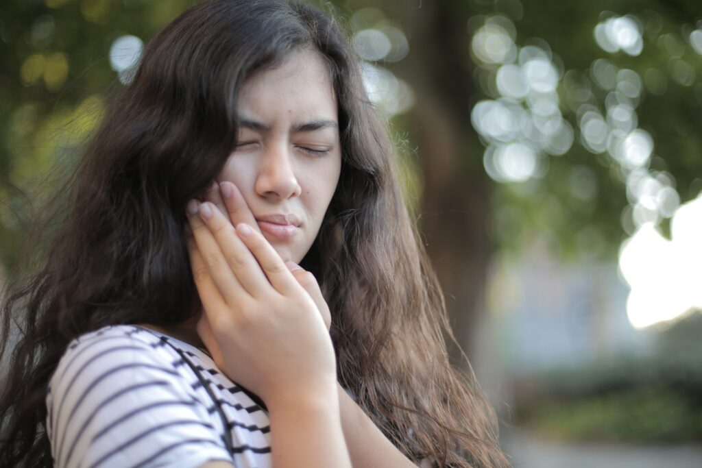 A woman holding her cheek in pain because of gum disease.