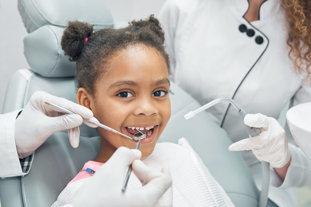 pediatric dentistry, little girls sits in dental chair
