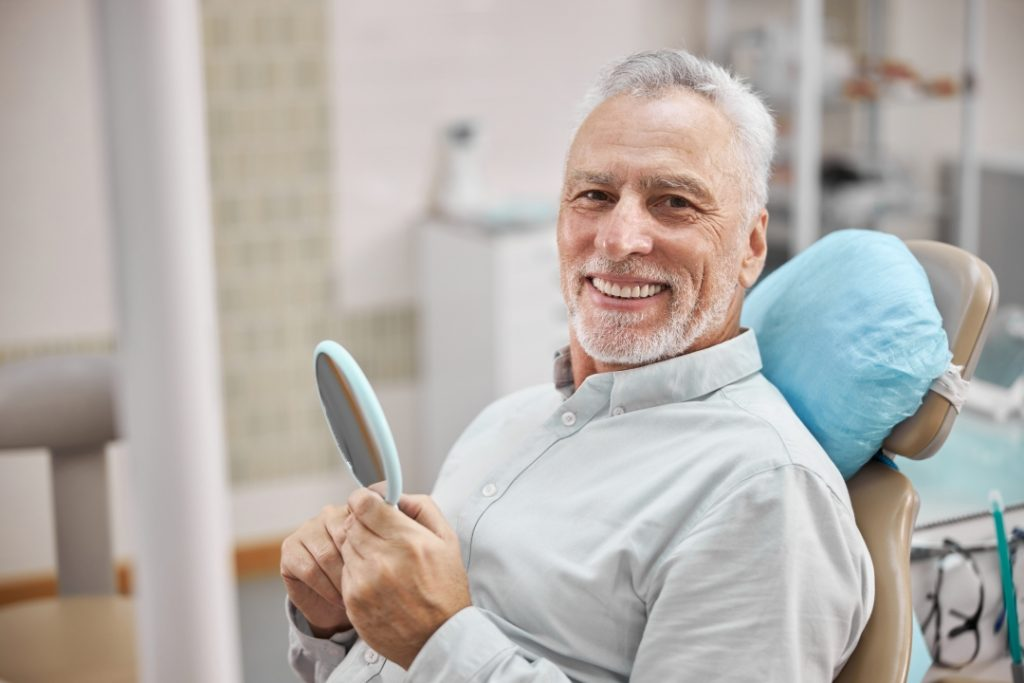 A man smiles after receiving dental restoration at a dental office.